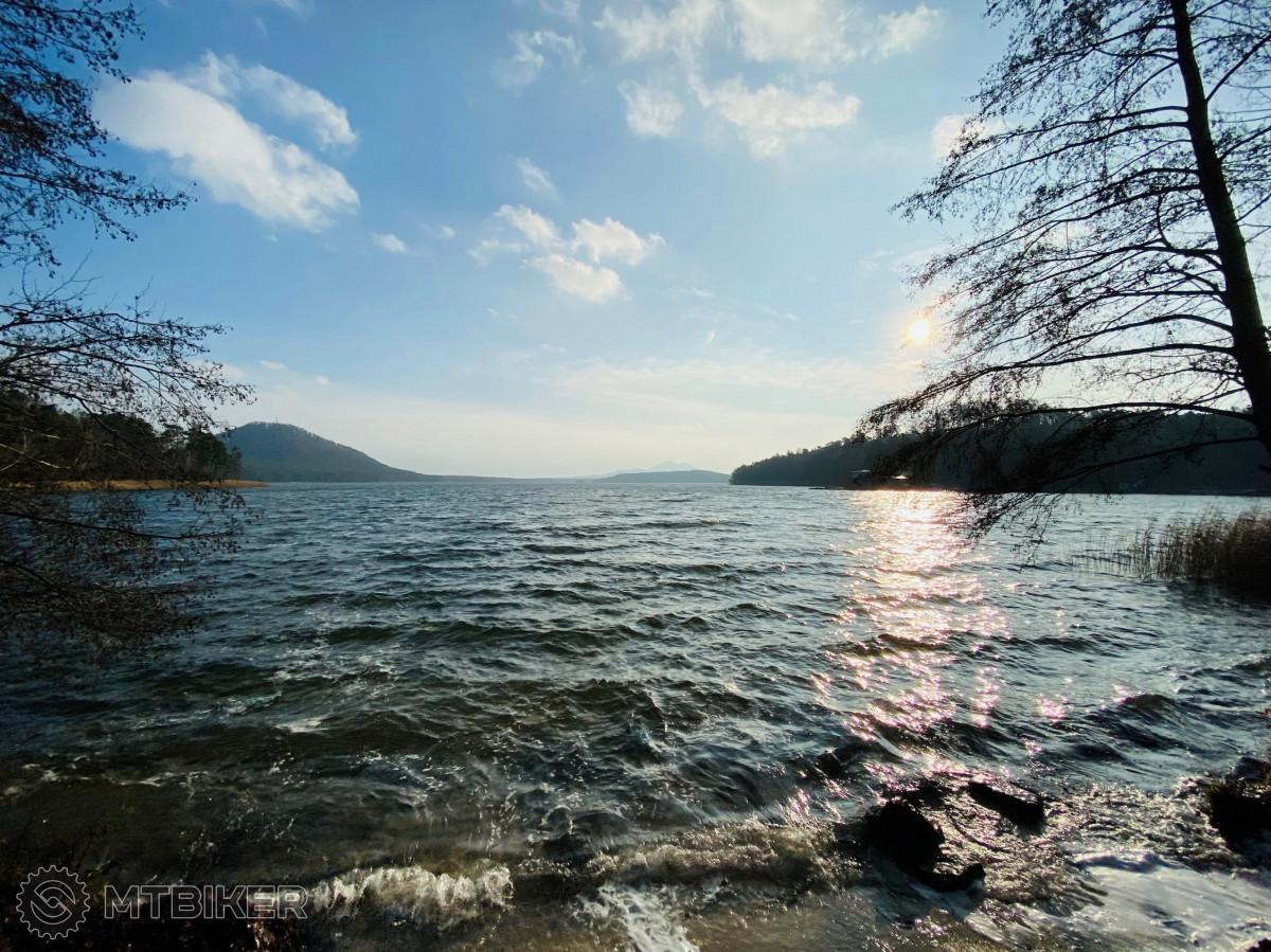 Sluncem ozářená hladina jezera s pohledem na Velký a Malý Bezděz.
