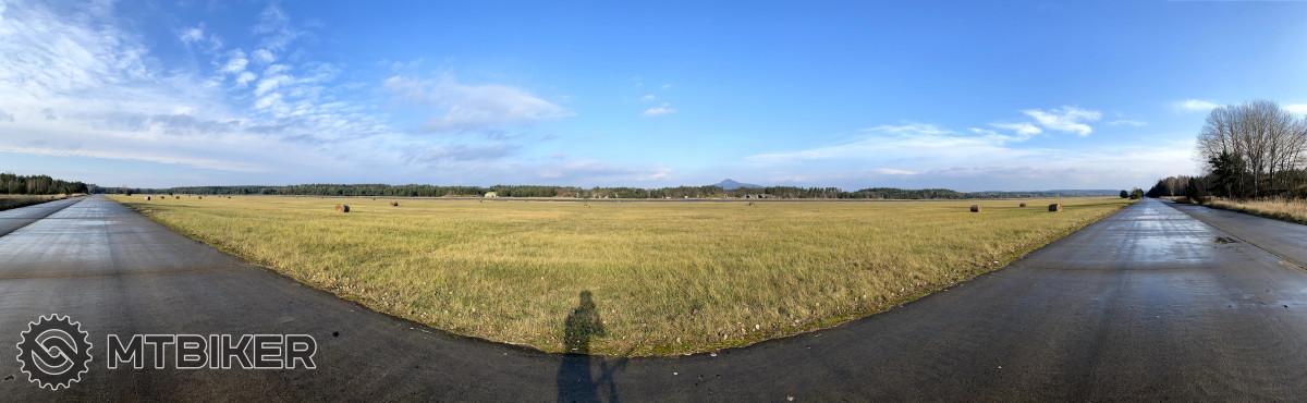Pojížděcí dráha letiště. V pozadí vrch Ralsko. Za dobré viditelnosti bývá vpravo pozorovatelný Ještěd.