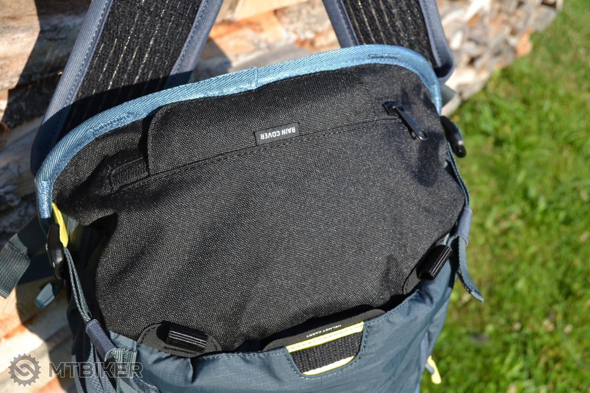 Kapsa na dně batohu skrývající pláštěnku a popruhy pro uchycení holenních chráničů.