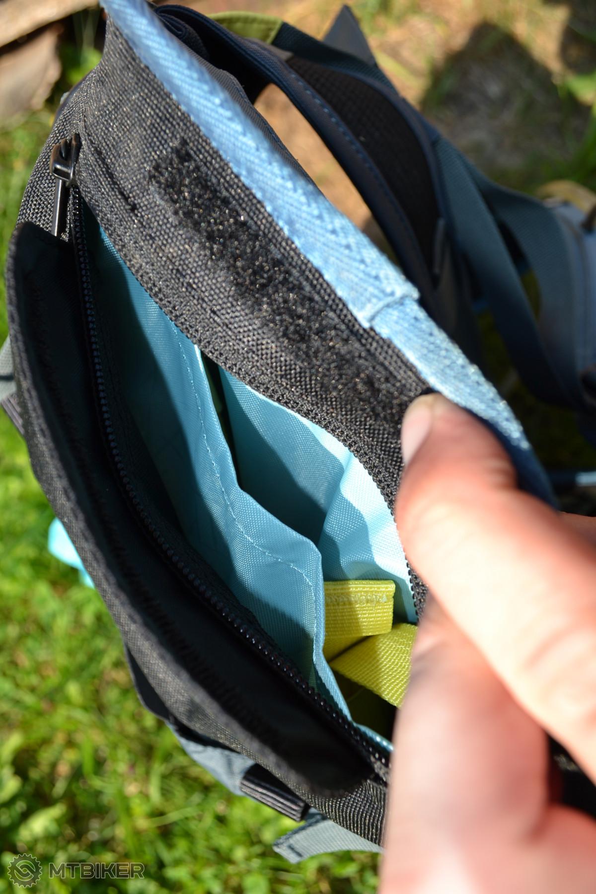 Kapsa na dně batohu je členěna na dvě poloviny - část pro pláštěnku a část pro popruhy.