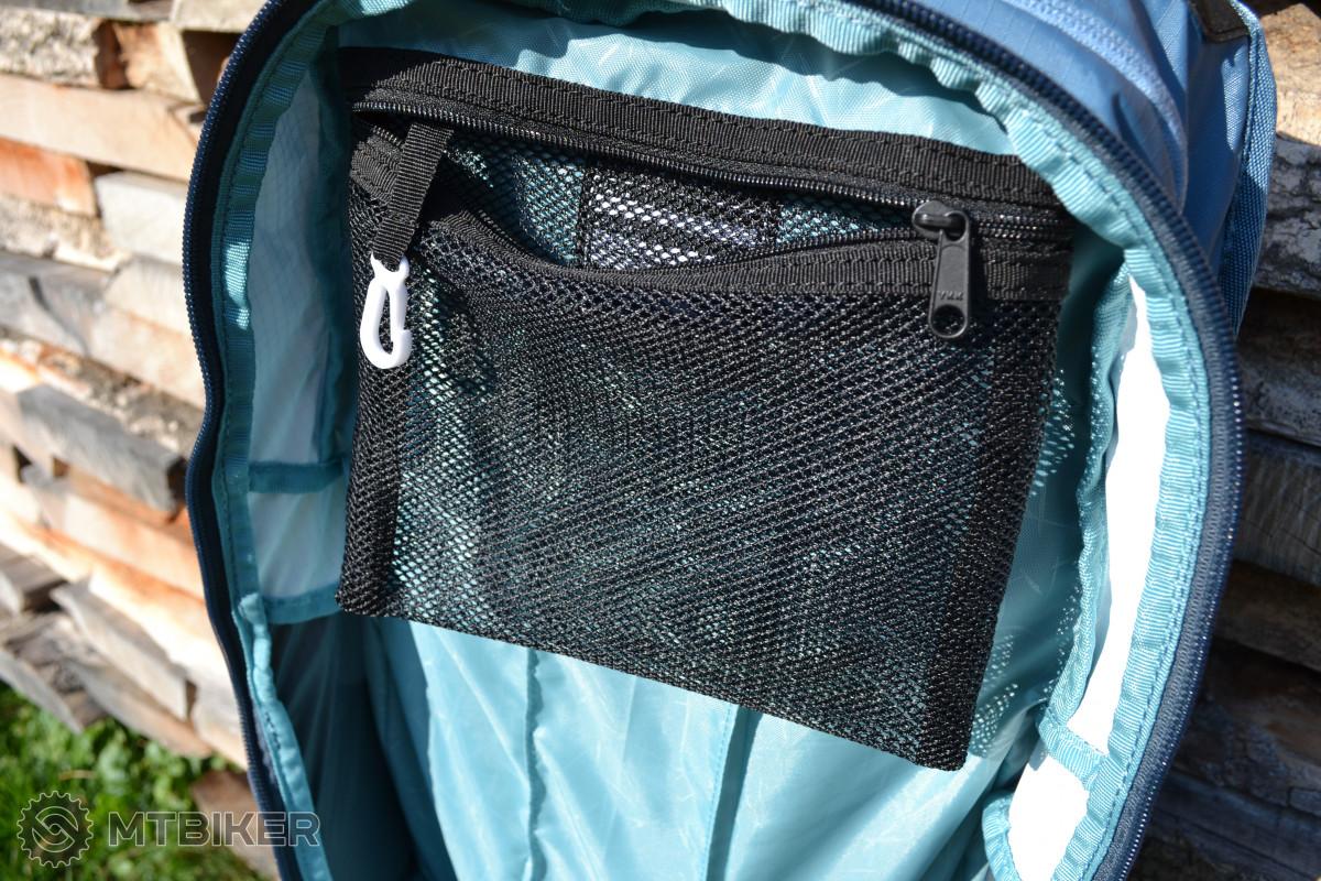Síťovaná kapsa s karabinou v horní části hlavního prostoru batohu.