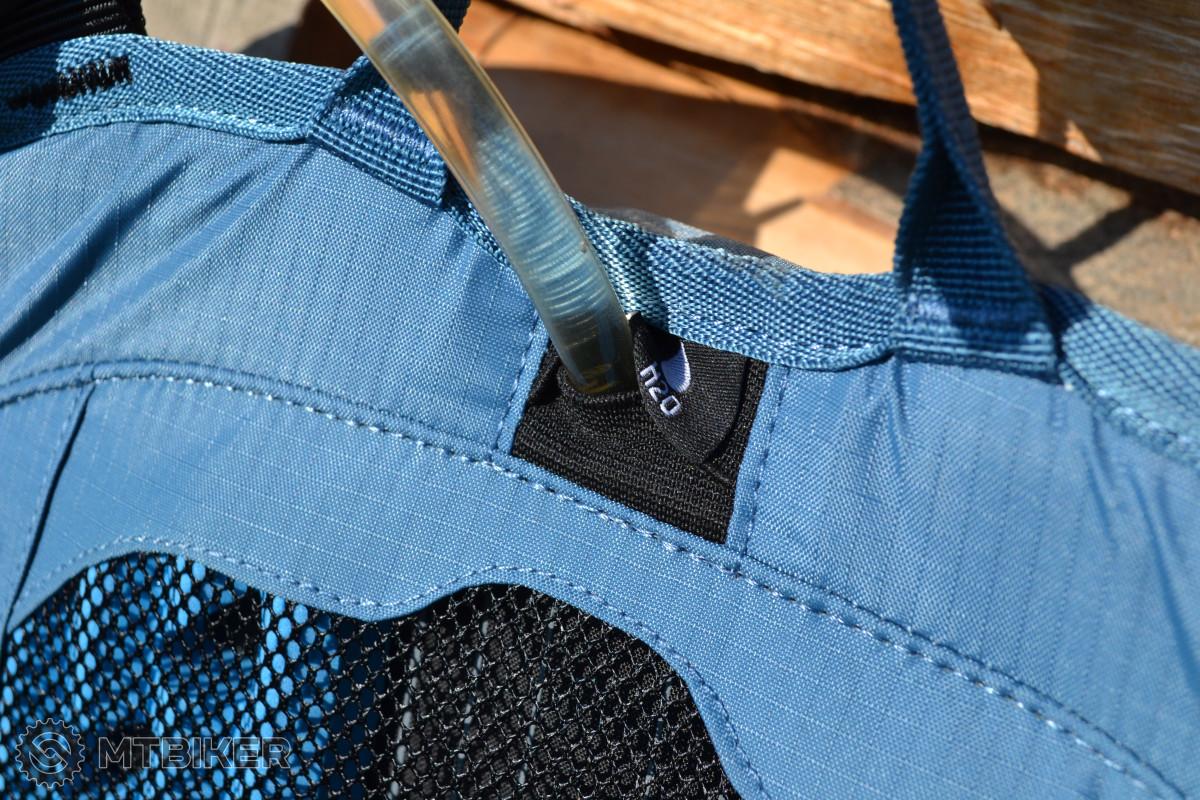 Průchodka pro hadičku pitného vaku se nachází uprostřed vršku zádové části, hadičku můžete vést po levém i pravém ramenním popruhu.